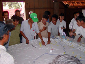Villagers discussing location names using the relief model as visual and tactile reference.